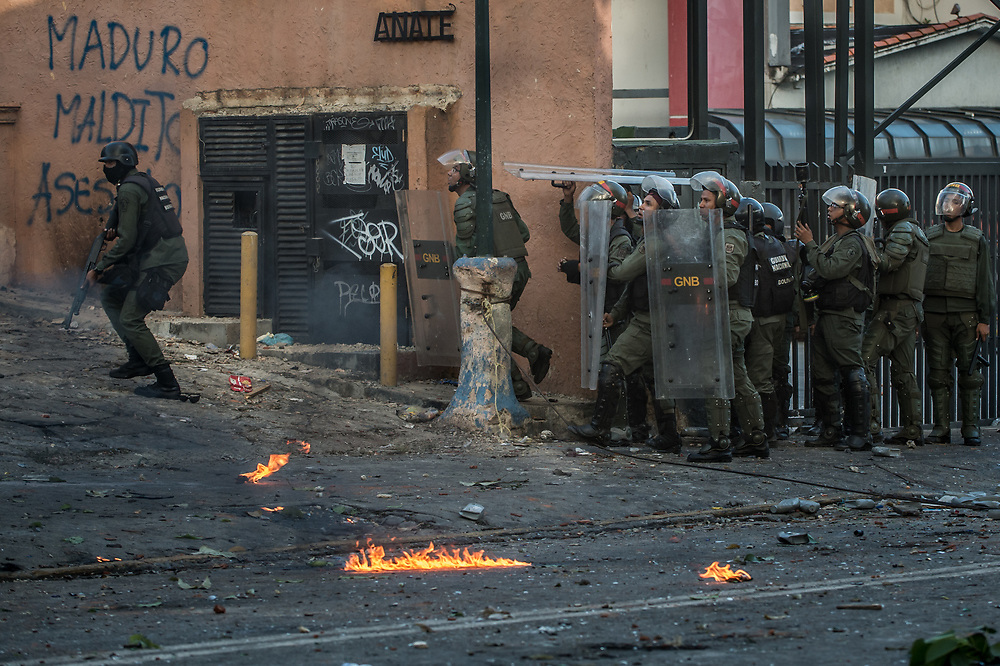 CARACAS, VENEZUELA - JULY 26, 2017: Soldiers chase protesters, shooting rubber bullets at them, during an anti-government protest to demand that the National Constituent Assembly election scheduled for Sunday, July 30th be cancelled. The political opposition called for a 48 hour national strike on July 26th and 27th, and for their supporters to close businesses, not go to work, and instead create barricades to block off their streets.  Opposition controlled areas of the country were completely shut down.  The strike was called as part of the opposition's civil resistance movement - that began on April 1st, to protest against the Socialist government's attempt to elect a new assembly that will have the power to re-write the constitution, and their opposition to the Socialist's continued threats to Venezuelan Democracy.  PHOTO: Meridith Kohut for The New York Times