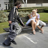 "An actor dressed up like a zombie runs next to a couple, on September 2, 2010, in the Northern Spanish city of Bilbao. Actors and dancers, dressed up like zombies, visited Bilbao to promote the musical show ""Forever, King of Pop"", based on Michael Jackson's ""Thriller"".  PHOTO/Rafa Rivas"