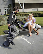 """An actor dressed up like a zombie runs next to a couple, on September 2, 2010, in the Northern Spanish city of Bilbao. Actors and dancers, dressed up like zombies, visited Bilbao to promote the musical show """"Forever, King of Pop"""", based on Michael Jackson's """"Thriller"""".  PHOTO/Rafa Rivas"""