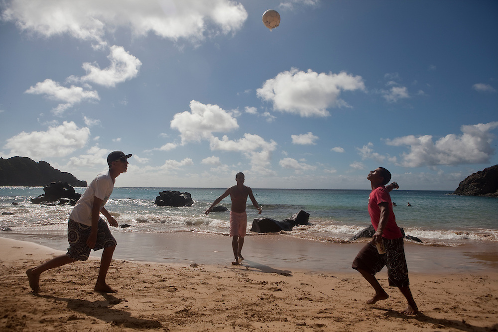 Young men playing football on a beach at Fernando de Noronha island, Brazil.