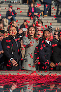 Laura Wright, joined by Ben Shepherd (L) and members of Vox Fortura (R), throws poppies in the fountain - Silence in the Square oraganised by the British Legion in Trafalgar Square  - 11 November 2016, London.