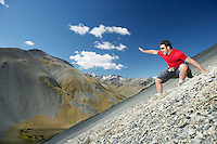 Man sliding down screen field in mountains