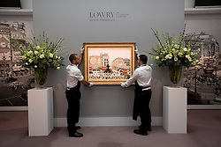 "© Licensed to London News Pictures. 21/03/2014. London, UK. Sotheby's auction house staff adjust ""Piccadilly Circus London"" (1960) (est. GB£4,000,000-6,000,000) by British artist LS Lowry during the press view for a new sale of the artist's work in London today (21/03/2014). The auction, entitled ""Lowry: The AJ Thompson Collection"", features works by Lowry assembled over a 30 year period by collector A.J. Thompson. Photo credit: Matt Cetti-Roberts/LNP"
