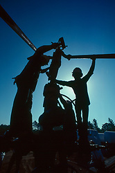 Oilfield workers assembling secondary recovery pipe onto christmas tree valve assembly in East Texas.