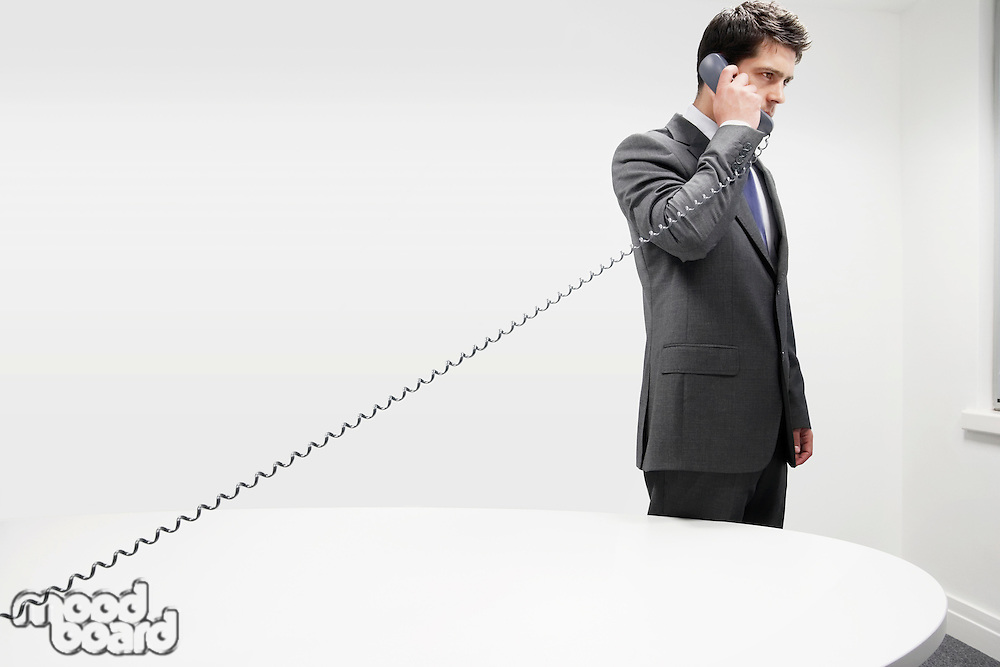 Businessman on Telephone by desk in office stretching receiver cord