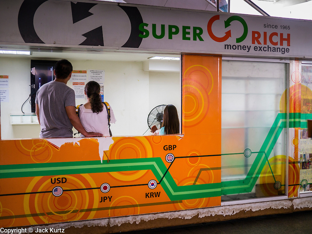 22 APRIL 2013 - BANGKOK, THAILAND: People wait to buy Thai Baht in a foreign currency exchange kiosk in Bangkok. The Thai Baht has gained markedly against the US Dollar, the Euro and Pound Sterling in recent months. On Monday, the Baht was trading at 28.57 Baht to 1 US Dollar on Apr. 22. The strengthening Baht means imported goods are cheaper in Thailand, but Thai exports cost more in other countries. It also means tourists and expats who live in Thailand have less money to spend as their currencies buy fewer Baht. The baht has risen 5 percent against the dollar this year to its highest level since before the Asian financial crisis in 1997. The Federation of Thai Industries, which has led calls for the authorities to act to lower the baht, said the rise in the past two weeks had been too rapid and its members were finding it hard to cope with the volatility because as the Baht appreciates their exports become more expensive. Thailand is among the world's leading exporters of rice, chicken, pork, electrical components, cars and is the leading exporter of canned tuna.    PHOTO BY JACK KURTZ