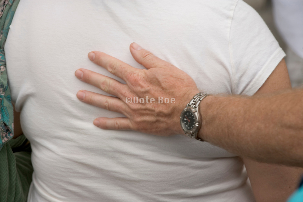 man gently laying his hand on the back of his wife