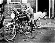 Dylan McNeil, 2, at left, and his brother Jordan,5, play on an old motorcycle in front of their motel rooms at the Town and Country Motel east of Greenfield. Since the rooms are so small the parking lot becomes the playground for dozen plus children who live at the motel. (Mike Fender Photo) w/ story