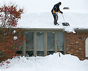 John Petrunyak  shovels snow off a neighbor's roof in Lancaster, New York, USA on Wednesday, November 19, 2014. Up to six feet of snow fell on the region Tuesday, stranding dozens of motorists on roadways and causing at least six deaths.
