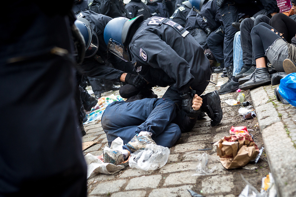 """Mit einem Großaufgebot hat die Berliner Polizei den Kiezladen """"Friedel 54"""" in Berlin Neukölln zwangsgeräumt. Bereits am Vorabend versammelten sich mehrere hundert Menschen vor dem Haus in der Friedelstraße 54. Direkt vor dem Eingang zum Kiezladen bildeten rund 100 Menschen eine Sitzblockade, um den direkten Zugang zu verhindern. Gegen halb neun Uhr morgens löste die Polizei die Blockade unter teils massiven Gewaltanwendung auf.  Dabei kam es auch mehrfach zur Behinderung von Pressevertretern. Gegen 13 Uhr verschaffte die Polizei sich schließlich Zugang zu den Räumlichkeiten des Kiezladens in dem sich zu diesem Zeitpunkt noch sechs Blockierer aufhielten. Diese wurden anschließend von Polizeibeamten aus dem Haus geführt. Die Räume im Erdgeschoss wurden nach Ende der polizeilichen Maßnahmen an den Gerichtsvollzieher übergeben."""