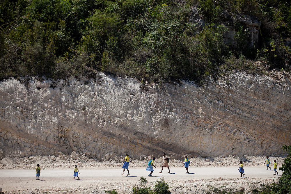 School children walk home from school on a section of road under construction above the town of Jeremie. The Inter-American Development Bank is funding this road project in the south of Haiti, aiming to cut travel time and transportation costs, and to improve living conditions in the southern provinces. This 50-mile stretch of road connects the small cities of Les Cayes and Jeremie and many rural villages in between. A Brazilian company, OAS, is doing the construction. The road is far from complete, but is already transforming commerce and daily life in the area. Travel time has been cut in half; fewer trucks are breaking down, so less food is spoiled; and farmers are planting more crops in anticipation of more dependable farm-to-market transportation.
