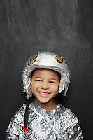 Portrait of young boy (5-6) in aluminum foil astronaut costume smiling studio shot