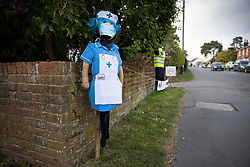 © Licensed to London News Pictures. 27/04/2020. Capel, UK. A scarecrow depiction of a nurse and a police officer stand at the front of a house in the Surrey village of Capel. Residents of the village have resurrected their summer tradition of scarecrows in tribute to NHS medical staff and other key workers. Up to 30 of the life size home made doll like characters can be seen in front gardens throughout the village. The public have been told they can only leave their homes when absolutely essential, in an attempt to fight the spread of coronavirus COVID-19 disease. Photo credit: Peter Macdiarmid/LNP