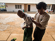 03 MARCH 2104 - MAE KASA, TAK, THAILAND:  A man helps his wife, who has TB, get back to their living space at the Sanatorium Center for Border Communities in Mae Kasa, about 30 minutes north of Mae Sot, Thailand. The Sanatorium provides treatment and housing for people with tuberculosis in an isolated setting for about 68 patients, all Burmese. The clinic is operated by the Shoklo Malaria Research Unit and works with several other NGOs that assist Burmese people in Thailand. Reforms in Myanmar have alllowed NGOs to operate in Myanmar, as a result many NGOs are shifting resources to operations in Myanmar, leaving Burmese migrants and refugees in Thailand vulnerable. Funding cuts could jeopardize programs at the clinic. TB is a serious health challenge in Burma, which has one of the highest rates of TB in the world. The TB rate in Thailand is ¼ to ⅕ the rate in Burma.        PHOTO BY JACK KURTZ
