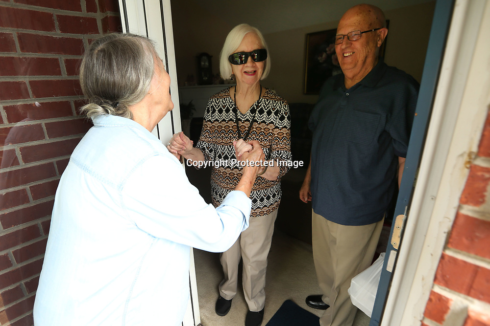 Judy Armentrout, with Meals on Wheels, is greeted by Jettie and Davis Norris as she drops off their meal during lunch on Wednesday.
