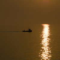 Golden sunset and fishing boat in the Firth of Forth, Scotland<br />
