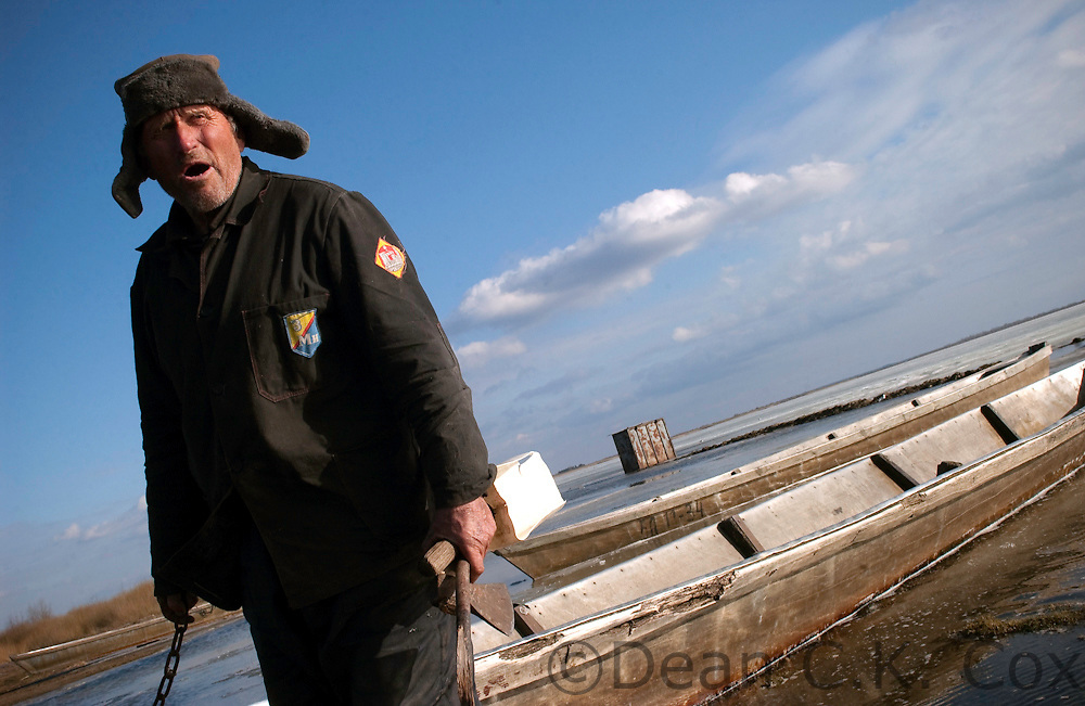 A fisherman clears ice from around his boat in preparation for spring fishing on a lake near the village of Sporova on April 1, 2006.