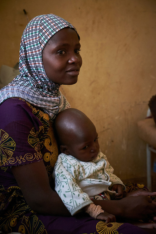 Assama Ousseini, 18 years old, with baby Maouia, 18 months old at the centre for Treatment of Acute Malnutrition with Complications (CRENI) of the Poudriere Hospital, Niamey, Niger on February 16, 2016. Assama comes from the village of Komo Bangou which is 100km from Niamey. Married when she was sixteen, Mauoia is her first child. She came with public transport to Niamey where she has a brother who could assist with the cost Maouia receiving adequate treatment. He has already improved after six days at the CRENI and has began to drink milk again. Every morning, a health worker comes to explain to Assama and other mothers correct practices for feeding a young child. Poudrière hospital is a reference hospital for the approximately 5 million people that live in the regions of Tilbery, Doss and Niamey with 581,000 children under 5 years. Constructed in 2002, it offers public health care, undertakes research and reinforces the capacity of medical staff. 37 doctors, 82 nurses and 22 midwives are employed at the hospital and have capacity of 146 beds with 72 of these in the paediatric section. Unicef supports the Therapeutic Nutritional Centre (TNC) for treating patients with severe acute malnutrition accompanied by complications (CRENI) which was rehabilitated in 2011 to treat 27 children. Since 2005, Unicef has supplied the hospital with ready-to-use therapeutic foods, medicine and training of healthcare workers.  In 2012, the last year of the nutrition crisis, 692 cases were treated with a recovery rate of 90%.