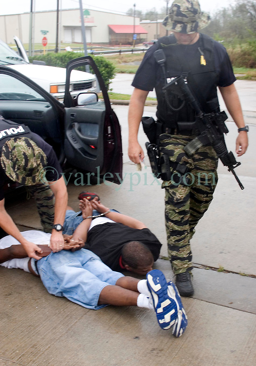 24 Sept, 2005.  Beaumont, Texas. Hurricane Rita. <br /> <br /> Police from the Beaumont rapid reaction force arrest looters who they captured breaking into a Chevron petrol station just off interstate 10.<br /> Photo; &copy;Charlie Varley/varleypix.com