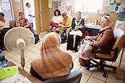 22 JUNE 2009 - PHOENIX, AZ: People wait to be called for their food boxes at the Cultural Cup Food Bank. The Cultural Cup has become a sort of community center. It started as a food bank and has since grown to include a clothing bank and free walk in clinic. The walk in clinic at the Cultural Cup Food Bank started two years ago when Cultural Cup founder Zarinah Awad wanted to expand the food bank's outreach and provide basic medical care for the people who use the food bank. The clinic sees, on average, 7 - 11 patients a week. Awad said that as the economy has worsened since the clinic opened and demand has steadily increased. She attributes the growth to people losing their jobs and health insurance. The clinic is staffed by volunteers both in the office and medical staff. Adults are seen every Saturday. Children are seen one Saturday a month, when a pediatrician comes in. Awad, a Moslem, said the food bank and clinic are rooted in the Moslem tradition of Zakat or Alms Giving, the giving of a small percentage of one's income to charity which is one of the Five Pillars of Islam.   PHOTO BY JACK KURTZ
