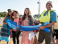 Hosts Patty and Mike Browher with their theme of the Lost River welcome Maxine Chen from Taiwan and Ana Ulibarri from Mexico at the Laconia Middle School as Up With People arrives Monday evening.  (Karen Bobotas/for the Laconia Daily Sun)
