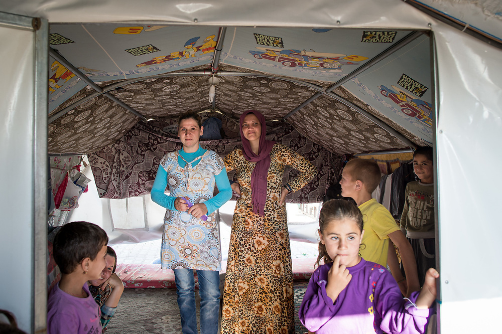 A family stands in their tent in the Yazidi refugee camp in Diyarbakir, June 11, 2015