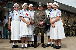Reenactor portraying German Hauptman doctor poses for a photograph with female members of the DRK (Deutsche Rote Kreuz)or German Red Cross at the Elsecar 1940s Weekend <br />