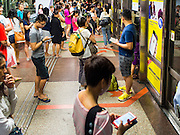 29 DECEMBER 2014 - SINGAPORE, SINGAPORE:  People wait to board a Singapore MRT Subway train on the NorthEast (NE) Line in Chinatown station. Singapore's subway system in 95 miles long and has more than 100 stations.    PHOTO BY JACK KURTZ