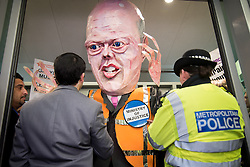 © Licensed to London News Pictures. 07/03/2014. Westminster, London, UK. An effigy of Justice Secretary Chris Grayling is held back as it attempts to gain entry to the Ministry of Justice, part of the Save UK justice protest against government-proposed legal aid cuts. Photo credit : David Tett/LNP