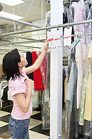 Side view of mid adult woman looking at clothing rack