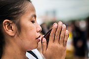 """22 JULY 2014 - BANGKOK, THAILAND: A Thai woman prays during a merit making ceremony at Sanam Luang. Hundreds of Thai military officers and civil servants attended a Buddhist chanting service and merit making ceremony to mark the 2nd month anniversary of the May 22 coup that deposed the elected civilian government and ended nearly six months of sometimes violent anti-government protests. The ruling junta said the ceremonies Tuesday were the kickoff to a """"Festival to Bring Back Happiness of the People of the Nation."""" There will be free concerts, historical pageants and movies at Sanam Luang, a large parade ground near the Ministry of Defense in Bangkok.    PHOTO BY JACK KURTZ"""