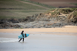 © Licensed to London News Pictures. 07/04/2020. Padstow, UK. A surfer walks across the beach at Constantine Bay on the north coast of Cornwall this afternoon. The weather in the south-west is forecast to be warm in the coming days. Photo credit : Tom Nicholson/LNP