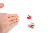 Cropped image of hands throwing gambling dice over white background