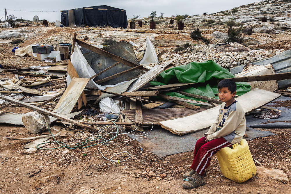 A boy sits atop a water can in front of the ruins of his family home, destroyed the day before. Dec. 28, 2013. West Bank, Palestinian Territories. (Photo by Gabriel Romero/Alexia Foundation ©2014)