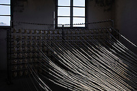 """SOVERIA MANNELLI, ITALY - 17 NOVEMBER 2016: Spools of wool are placed here on an old warping mill at the Lanificio Leo woolen mill in Soveria Mannelli, Italy, on November 17th 2016.<br /> <br /> Lanificio Leo was the first and last machine-operated woolen mill of Calabria, founded in 1873, it employed 50 people until the 1970s, when national policies to develop Italy's South cut out small businesses and encouraged larger productions or employment in the public administration.<br /> <br /> The woolen mill was on stand-by for about two decades, until Emilio Salvatore Leo, 41, started inviting international designers and artists to summer residencies in Soveria Mannelli. With their inspiration, he tried to envision a future for his mill and his town that was not of a museum of the past,<br /> Over the years, Mr. Leo transformed his family's industrial converter of Calabrian wool into a brand that makes design products for home and wear. His century old machines now weave wool from Australia or New Zealand, cashmere from Nepal and cotton from Egypt or South America. He calls it a """"start-up on scrap metals,"""" referring to the dozens of different looms that his family acquired over the years.<br /> <br /> Soveria Mannelli is a mountain-top village in the southern region of Calabria that counts 3,070 inhabitants. The town was a strategic outpost until the 1970s, when the main artery road from Naples area to Italy's south-western tip, Reggio Calabria went through the town. But once the government started building a motorway miles away, it was cut out from the fastest communications and from the most ambitious plans to develop Italy's South. Instead of despairing, residents benefited of the geographical disadvantage to keep away the mafia infiltrations, and started creating solid businesses thanks to its administrative stability, its forward-thinking mayors and a vibrant entrepreneurship numbering a national, medium-sized publishing house, a leading school furniture manufactu"""