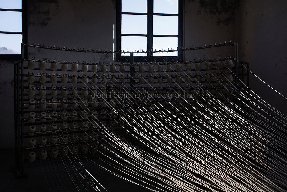 SOVERIA MANNELLI, ITALY - 17 NOVEMBER 2016: Spools of wool are placed here on an old warping mill at the Lanificio Leo woolen mill in Soveria Mannelli, Italy, on November 17th 2016.<br /> <br /> Lanificio Leo was the first and last machine-operated woolen mill of Calabria, founded in 1873, it employed 50 people until the 1970s, when national policies to develop Italy&rsquo;s South cut out small businesses and encouraged larger productions or employment in the public administration.<br /> <br /> The woolen mill was on stand-by for about two decades, until Emilio Salvatore Leo, 41, started inviting international designers and artists to summer residencies in Soveria Mannelli. With their inspiration, he tried to envision a future for his mill and his town that was not of a museum of the past,<br /> Over the years, Mr. Leo transformed his family&rsquo;s industrial converter of Calabrian wool into a brand that makes design products for home and wear. His century old machines now weave wool from Australia or New Zealand, cashmere from Nepal and cotton from Egypt or South America. He calls it a &ldquo;start-up on scrap metals,&rdquo; referring to the dozens of different looms that his family acquired over the years.<br /> <br /> Soveria Mannelli is a mountain-top village in the southern region of Calabria that counts 3,070 inhabitants. The town was a strategic outpost until the 1970s, when the main artery road from Naples area to Italy&rsquo;s south-western tip, Reggio Calabria went through the town. But once the government started building a motorway miles away, it was cut out from the fastest communications and from the most ambitious plans to develop Italy&rsquo;s South. Instead of despairing, residents benefited of the geographical disadvantage to keep away the mafia infiltrations, and started creating solid businesses thanks to its administrative stability, its forward-thinking mayors and a vibrant entrepreneurship numbering a national, medium-sized publishing house, a leading school furniture manufacturer and an ancient woolen mill