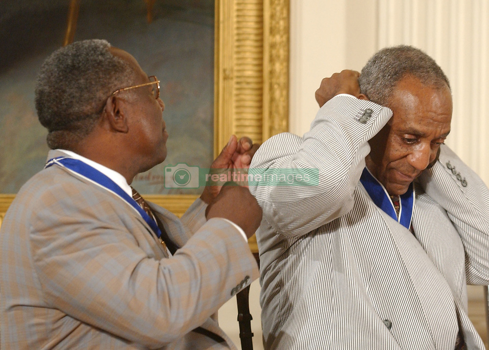 Bill Cosby admires his Presidential Medal of Freedom that he received from United States President George W. Bush during a ceremony in the East Room of the White House in Washington, D.C. on July 9, 2002..Credit: Ron Sachs / CNP. 09 Jul 2002 Pictured: Hank Aaron offers a helping hand to Bill Cosby after the latter received the Presidential Medal of Freedom from United States President George W. Bush during a ceremony in the East Room of the White House in Washington, D.C. on July 9, 2002..Credit: Ron Sachs / CNP. Photo credit: Ron Sachs / CNP / MEGA TheMegaAgency.com +1 888 505 6342