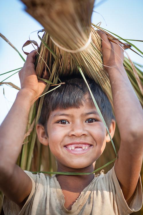 Countryside boy carrying harvest overhead (Myanmar)