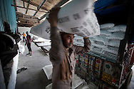 Workers carry bags of sugar to be shipped out at Simbhaoli Sugars factory in in Hapur District in Uttar Pradesh, India on April 2, 2014. The plant, contracted with 50,000 local sugarcane farmers, produces about 9500 tons of sugar per day including bulk sugar,pharmaceutical sugar, candy sugar and raw sugar. Uttar Pradesh is the 2nd largest sugar production state in India following Maharashtra. <br /> (Kuni Takahashi/Bloomberg)