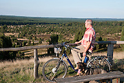 Heidelandschaft, Radfahrer auf Aussichtspunkt Wilseder Berg, Weg, bluehendes Erika, Wacholder, Wilsede, Naturschutzpark Lueneburger Heide, Niedersachsen, Deutschland.| .moorland Totengrund, heather, junipers, track, cyclist on viewpoint Wilseder Berg, Wilsede, moorland Lueneburger Heide near Wilsede, Lower Saxony, Germany.