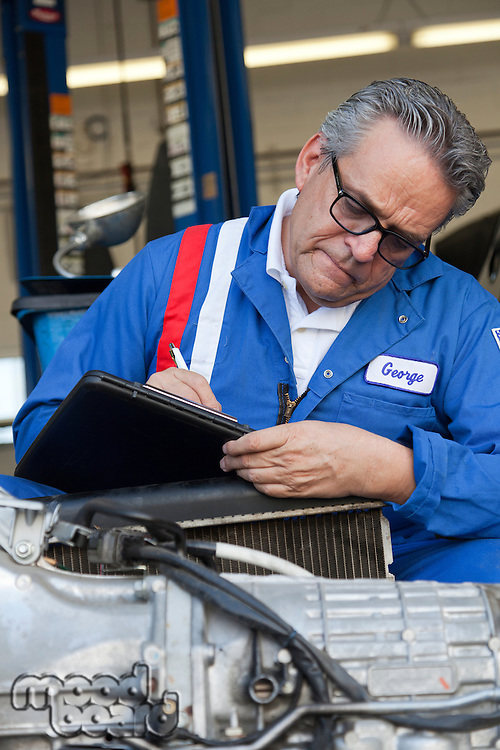 Mechanic writing down something on clipboard