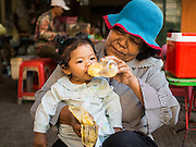 27 FEBRUARY 2015 - PHNOM PENH, CAMBODIA: A woman feeds her daughter in Phnom Penh.   PHOTO BY JACK KURTZ