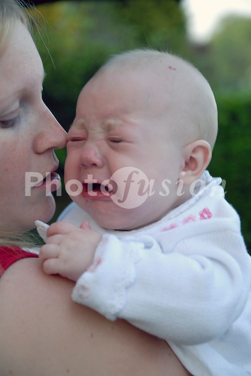 Crying baby & young mother UK