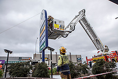 Auckland-Aerial fire truck used to remove sign damaged by wind gusts