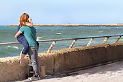 Israel, Tel Aviv, couple hugging at the renovated promenade in the old port, now an entertainment centre
