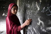 Rabihat, 12 years scribbles graffiti on the burnt walls of her classroom.  Her school that was first burnt and then bombed by the taliban shortly after the singing of the peace accord on 18th February 2009 in  Nazarabad near Matta, SWAT. ..Rabihat looks forward to returning to school but as yet funding for new premises and books, resources etc has not materialised from central government..