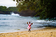 A young girl carrying two coconuts at Piscina Beach (Pool Beach) in São Tomé island.
