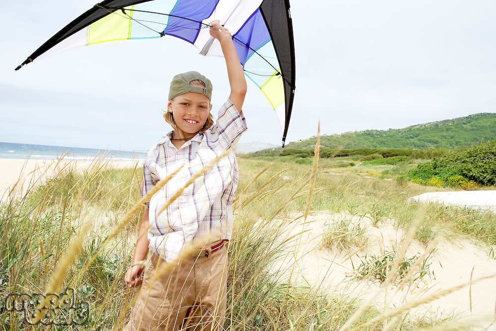 Pre-teen boy arms raised holding kite above head on beach