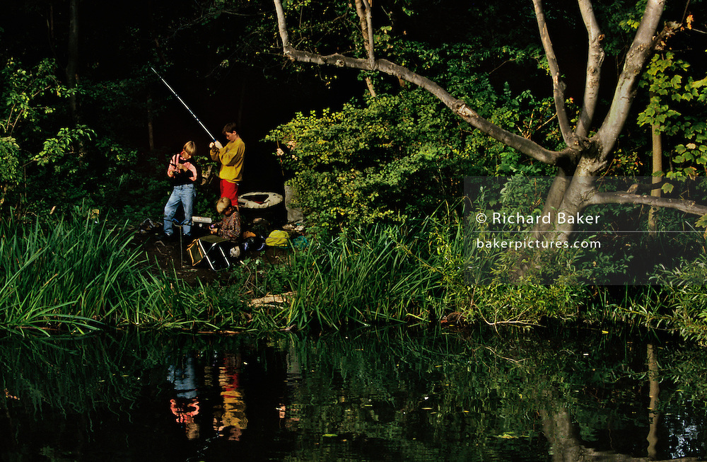 Three teenage boys bait their lines in the calm of the River Wandle, one of London's lost rivers that still meanders through inner-city London on its course from Carshalton Pond to the Thames. The three lads are reflected in the ripples of this once-polluted water which was once flushed with the toxins of industry such as tanning factories and breweries. After expensive clean-ups by local authorities, kids like these are once again able to catch trout in the way boys like them would do hundreds of years before the industrial revolutiion fouled many a water course. It is a perfect later-summer afternoon and the sun is shining on waterside reeds and grasses making this a scene of idyllic boyhood and undusturbed lazy dreams.