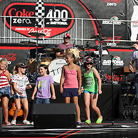 Pat Monahan of the Grammy award winning band Train sings with kids from the crowd during a one hour performance prior to the start of the NASCAR Coke Zero 400 race at Daytona International Speedway in Daytona Beach, Fl., on Saturday July 7, 2012. (AP Photo/Alex Menendez) Grammy Award winning band TRAIN plays an hour long concert prior to the NASCAR Coke Zero 400 race at Daytona International Speedway in Daytona Beach, Florida on July 7, 2012.
